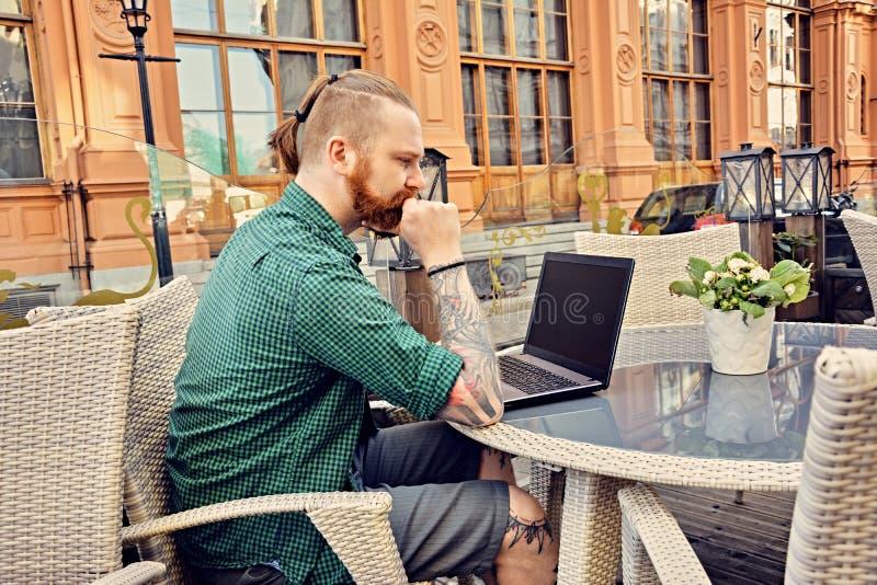 Tatuerad manlig användande bärbar dator i ett öppet gatakafé fotografering för bildbyråer