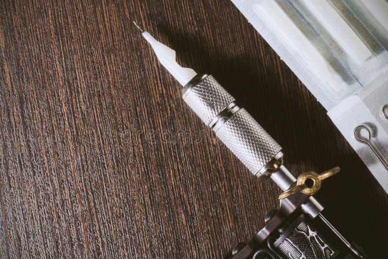 Tatueringmaskin på träbakgrundscopyspace arkivbild