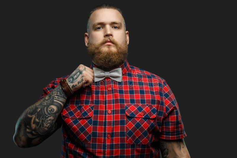 Tatuująca brodata unformal samiec w czerwonej koszula i popielatym łęku krawacie zdjęcia royalty free