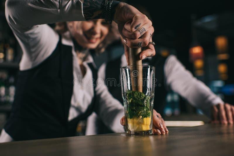 tatuującemu żeńskiemu barmanu koledze pokazywać dlaczego przygotowywać napój obraz royalty free