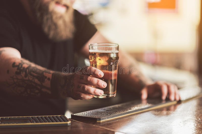 Tatuujący barman z brodą pracuje w pubie zdjęcie royalty free