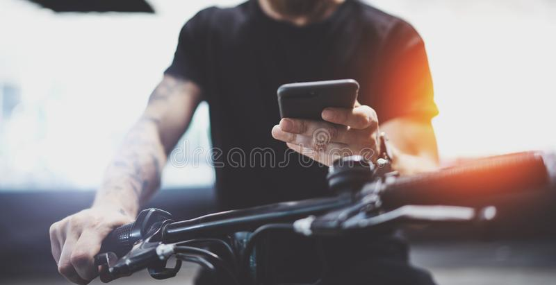 Tatuujący mięśniowy męski mienie telefon komórkowy w rękach i używać mapy app dla przygotowywać przejażdżki drogową trasę Odkrywa obraz stock