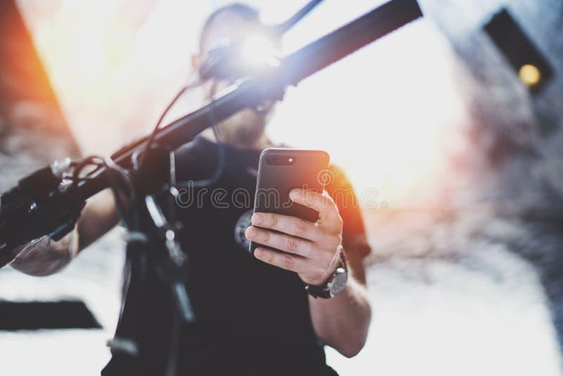 Tatuujący mięśniowy męski mienie telefon komórkowy w rękach i używać mapy app dla przygotowywać przejażdżki drogową trasę Odkrywa zdjęcie royalty free