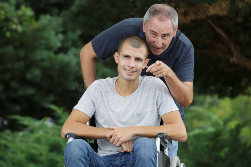 Taty i syna obsiadanie w wózku inwalidzkim outdoors zdjęcia stock