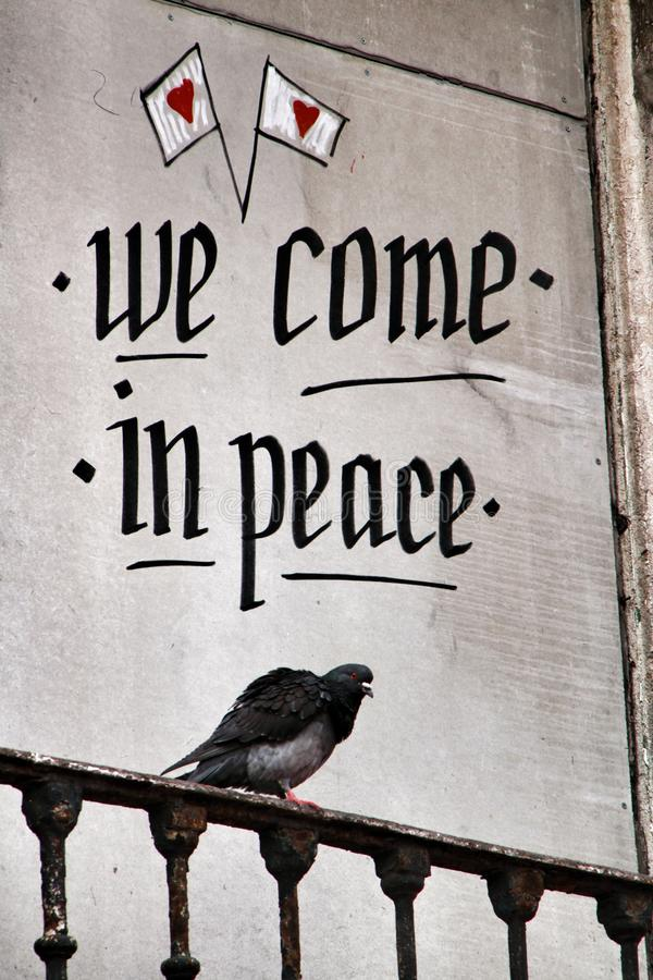 Taube gehockt auf einem Balkon mit Friedensmitteilung lizenzfreie stockbilder