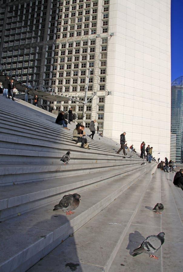 Tauben und Leute auf der Treppe des Grande Arche im La-Verteidigungsbezirk in Paris lizenzfreie stockfotografie