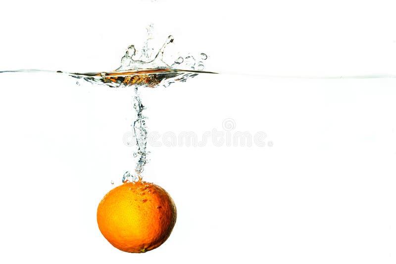 Tauchen der frischen Frucht in kaltes Wasser mit Spritzen und Blasen stockfoto