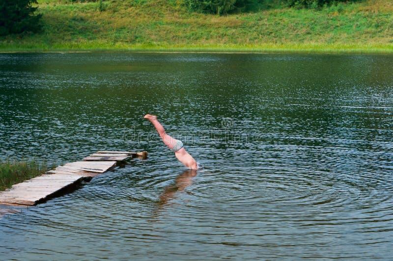 Tauchen Sie vom Pierkopf unten, springen Sie in das Wasser lizenzfreies stockbild