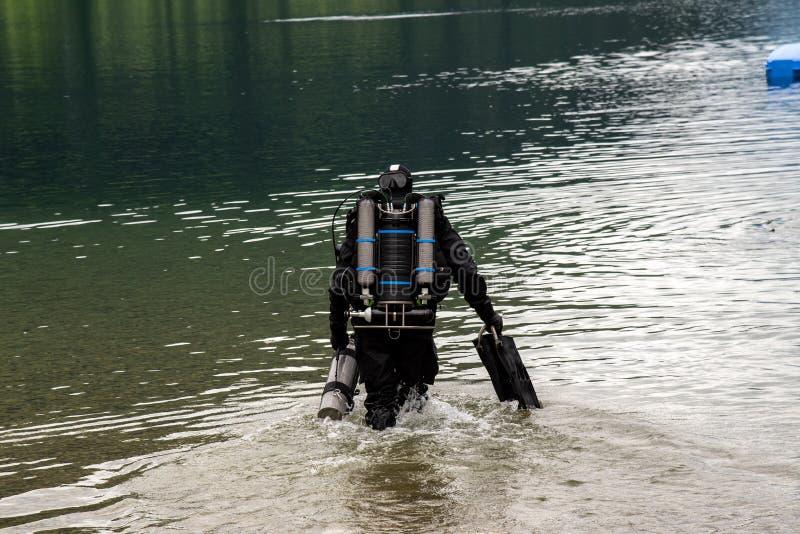 Taucher, der den See in hohe Alpen Österreich betritt lizenzfreie stockfotografie