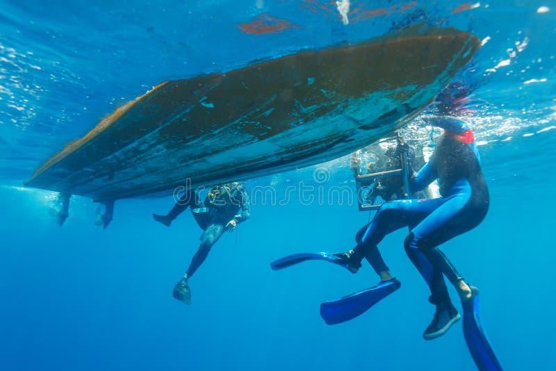 Taucher, die in Boot klettern lizenzfreie stockfotos