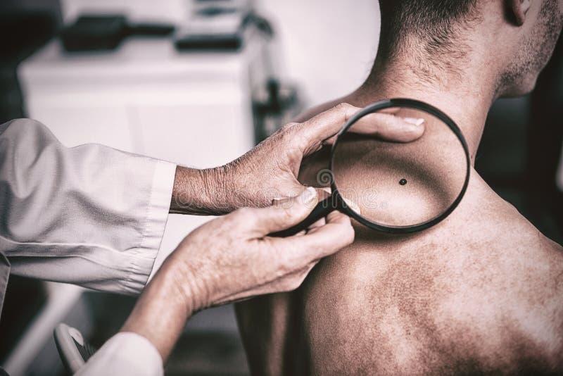 Taupe de examen de dermatologue avec la loupe images stock