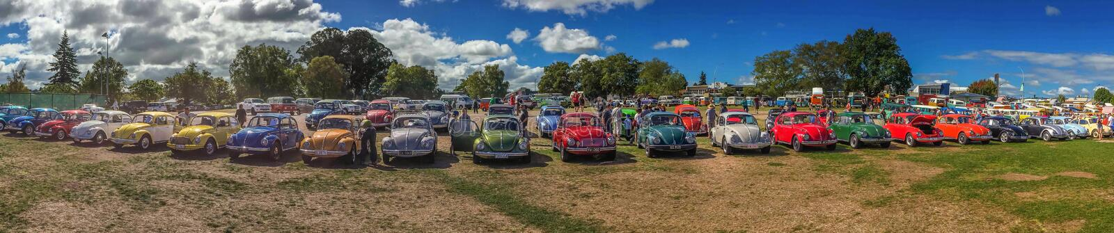 Taupo, New Zealand, April, 14, 2015: A sweeping panoramic view of a row of brighly coloured vintage beetle at a auto show stock image