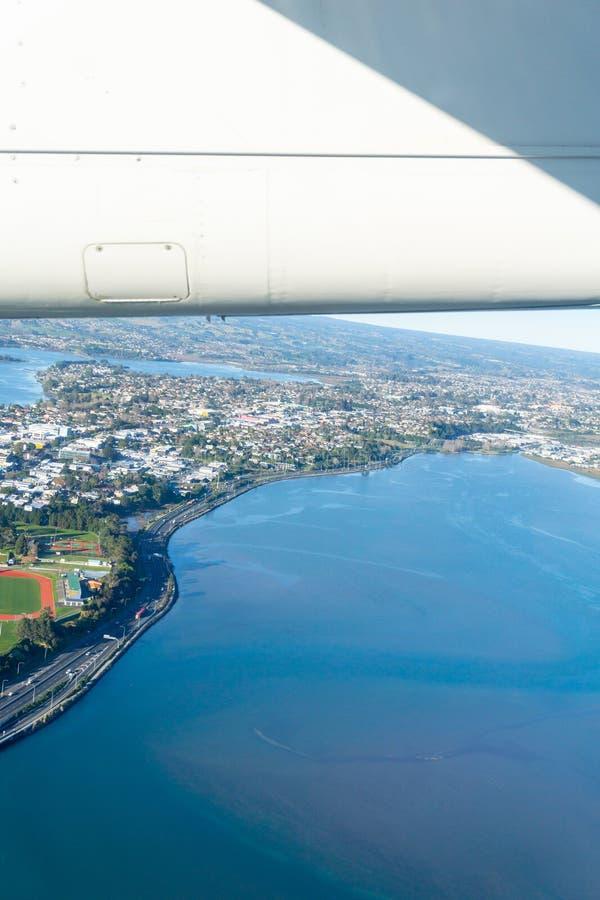 Tauranga harbour and urban peninsula aerial image with plane win. Tauranga harbour and urban peninsula aerial image city stretching to distant horizon over land stock photos