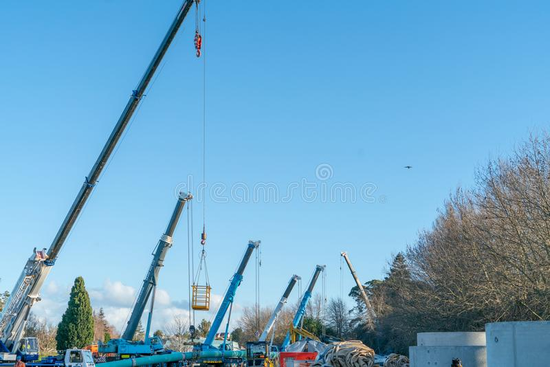 Cranes and plant at Memorial Park Southern Pipeline project base. TAURANGA, NEW ZEALAND - JULY 23 2018; several cranes and plant at Memorial Park Southern royalty free stock images