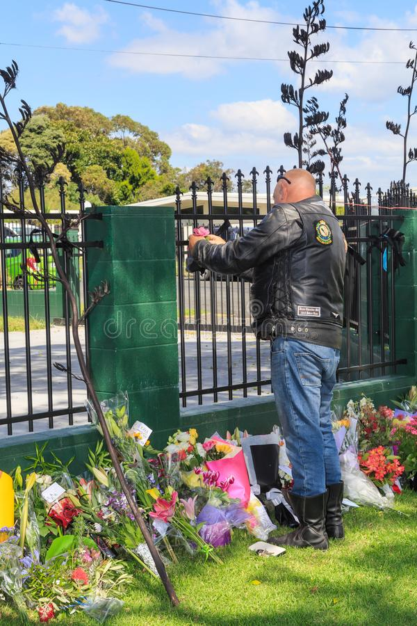 A biker tying a flower to a memorial for the victims of the March 15, 2019 Christchurch shootings royalty free stock photo