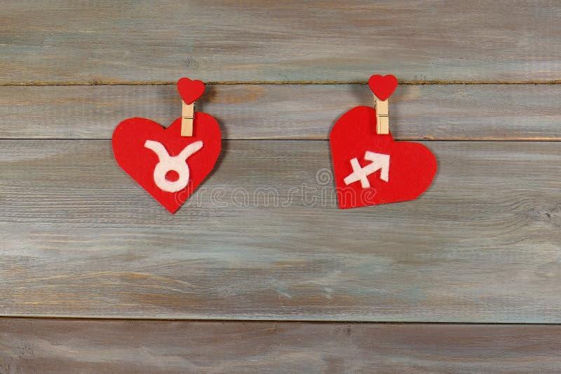 Tauro y sagitario muestras del zodiaco y del corazón Vagos de madera imágenes de archivo libres de regalías