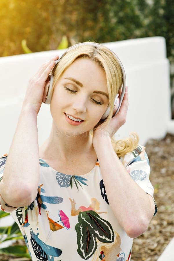 Tausendjähriges weißes Mädchen hört Musik auf Kopfhörern beim im warmen Licht draußen lächeln stockfotografie