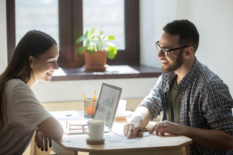 Tausendjährige Angestellte, die erfolgreichen Unternehmensplan im offi besprechen lizenzfreie stockfotos