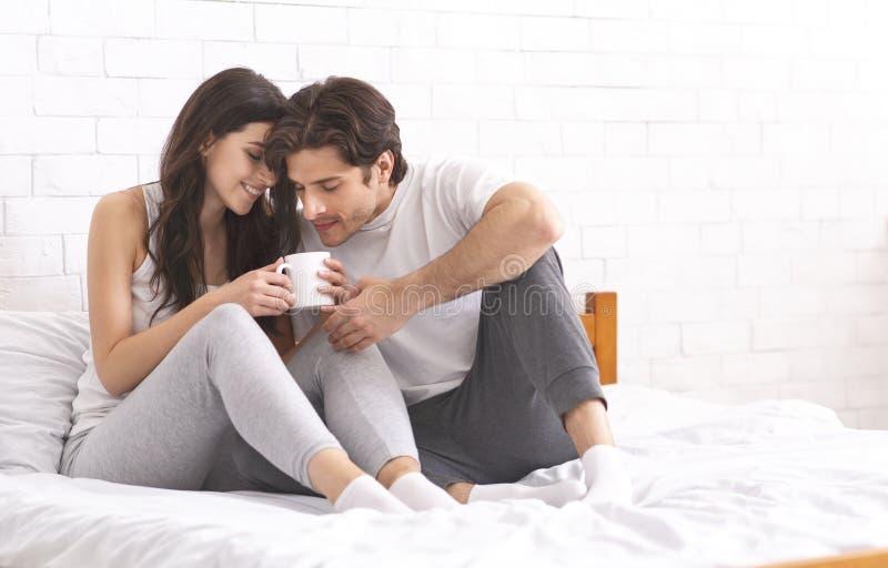 Tausendjährige Jungvermählten, die Schale frischen Kaffee im Bett teilen stockfoto