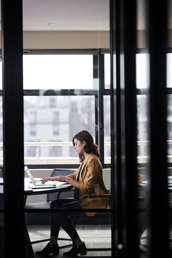 Tausendjährige weiße kreative Geschäftsfrau, die allein in einem Konferenzzimmer, vertikal arbeitet stockfoto