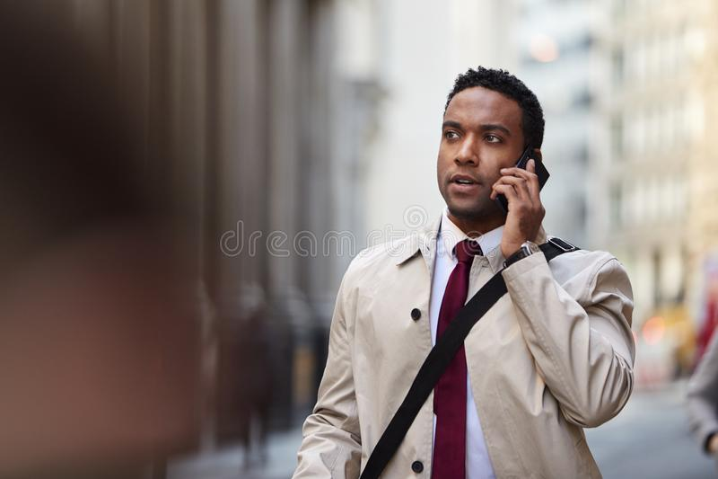Tausendjähriger schwarzer Geschäftsmann, der oben in eine beschäftigte London-Straße unter Verwendung des Smartphone, Abschluss g stockfoto