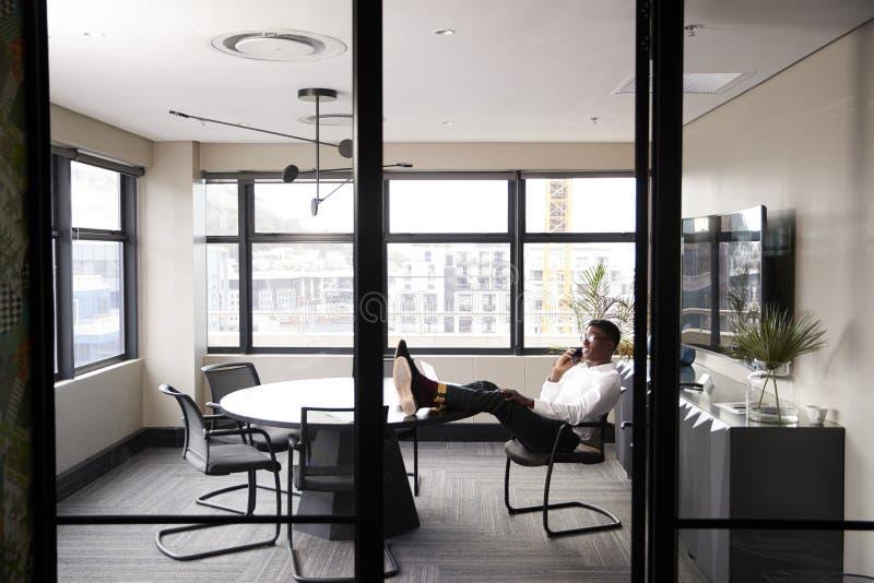 Tausendjähriger schwarzer Geschäftsmann, der am Telefon mit Füßen oben auf einem Schreibtisch, gesehen vom Eingang spricht stockfotos