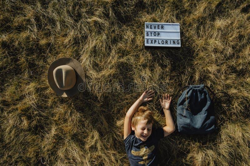 Tavel feliz com criança Menino de sorriso que encontra-se na grama do outono exterior fotos de stock royalty free