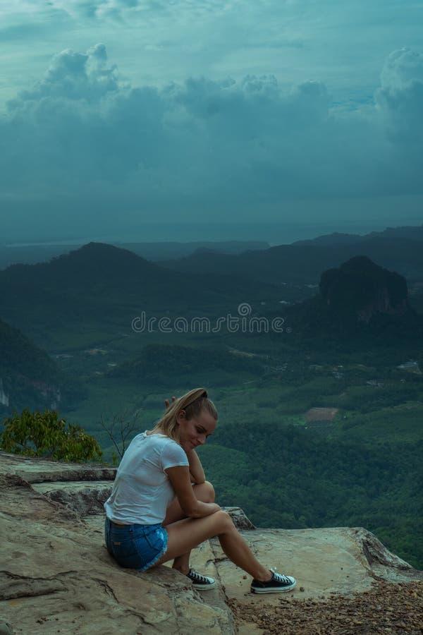 Taveler de la mujer que se sienta en el acantilado imagen de archivo
