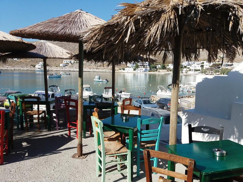 Taverna. Summer, greece, folegandros, tables, ummbrelas, sea, boats, green, outdoor, holiday, cyclades, egee, chairs, white, colorful, nopeople, june stock photography