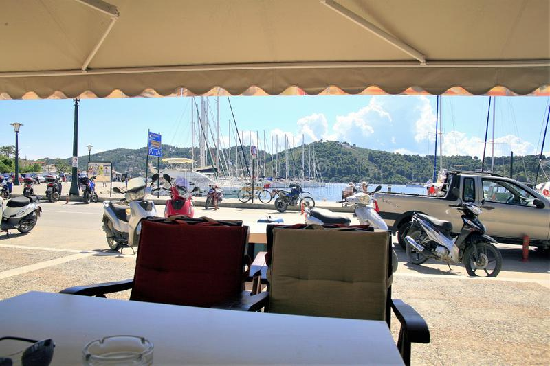 Taverna View, Skiathos town, Greece. Skiathos, Greece. June 20, 2014. View from the seat of a taverna of holidaymakers and locals enjoying the new harbor quay at royalty free stock photography