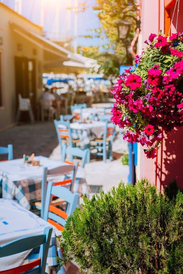 Taverne colorée vive grecque traditionnelle avec les fleurs pourpres sur la rue méditerranéenne étroite le jour chaud d'été images stock