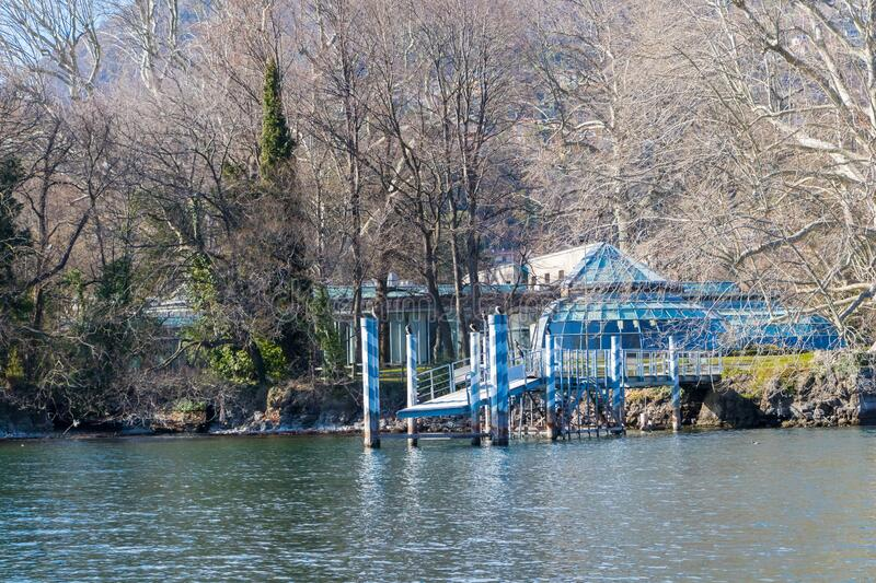 The small town of Tavernola with small boat dock at lake Como in Italy. Tavernola, Italy - March 10, 2019: The small town of Tavernola with small boat dock at stock photography