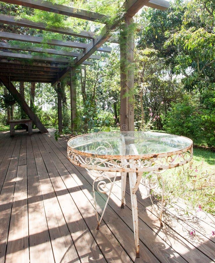 Tavola arrugginita del ferro battuto sul patio soleggiato immagine stock