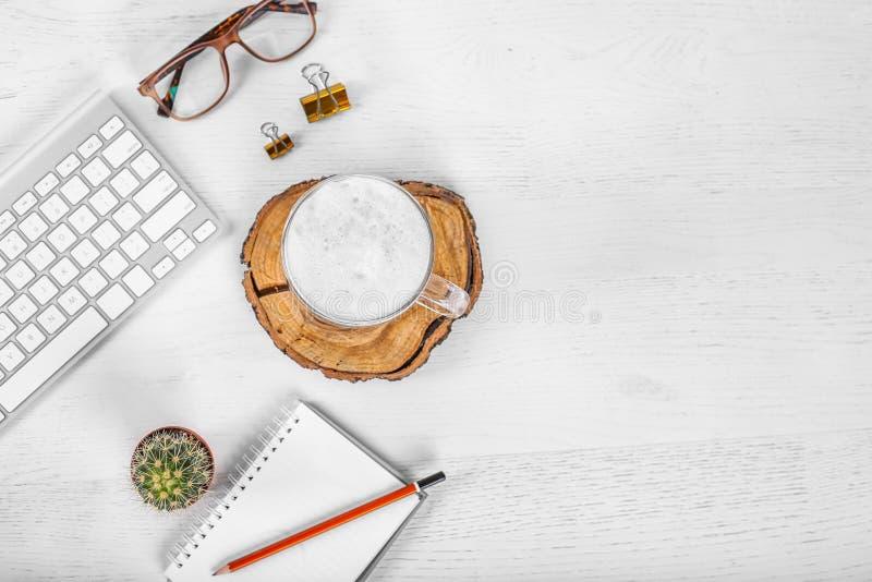 Tavola bianca della scrivania con il topo e tastiera del computer, tazza del caffè del latte, matite e vetri dell'occhio Vista su fotografie stock libere da diritti