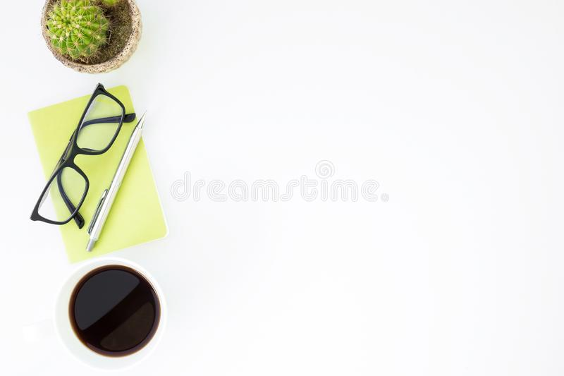 Tavola bianca della scrivania con la tazza di caffè, il taccuino ed i rifornimenti Vista superiore con lo spazio della copia, dis fotografie stock libere da diritti