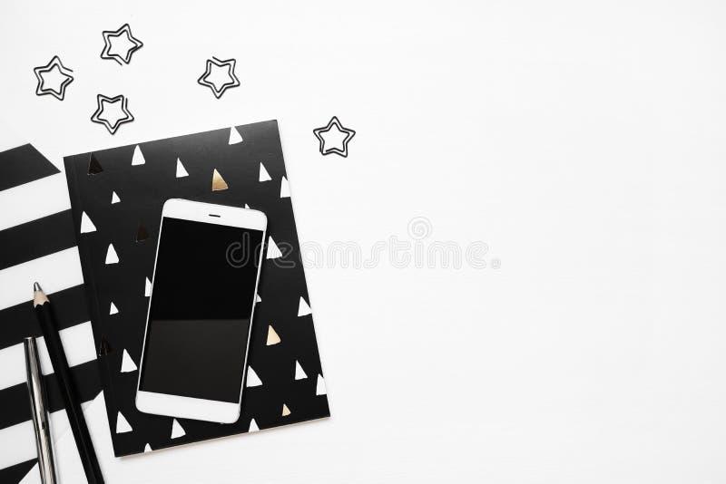 Tavola bianca moderna della scrivania con il taccuino alla moda, lo smartphone ed altre stelle delle clip dei rifornimenti Copi l immagine stock