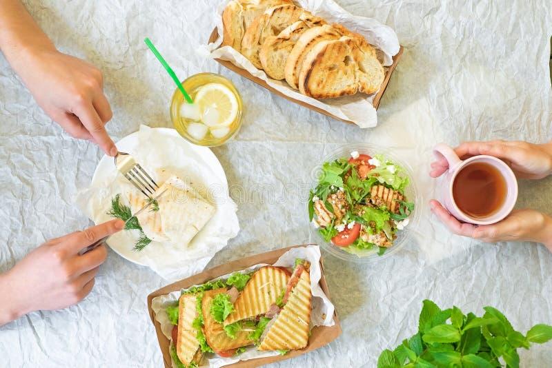 Tavola con le mani, vista superiore dei panini dell'insalata di Caesar, di Bruschetta, del prosciutto e del pomodoro da sopra fotografie stock