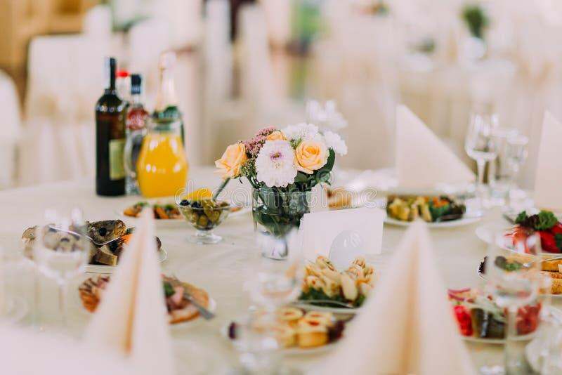 Tavola con precisione servita del ristorante di banchetto con gli spuntini, la coltelleria, il vino, i vetri e la decorazione del immagine stock libera da diritti