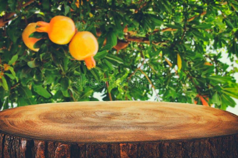 Tavola d'annata del bordo di legno davanti al paesaggio vago dell'albero di melograno immagini stock libere da diritti