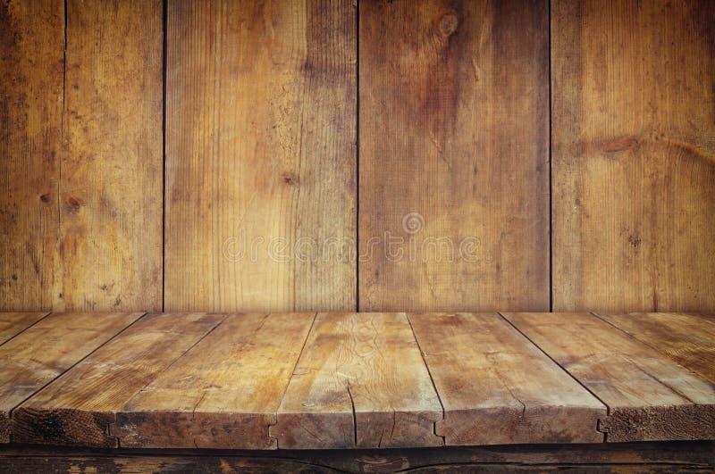 Tavola d'annata del bordo di legno di lerciume davanti a vecchio fondo di legno Aspetti per i montaggi dell'esposizione del prodo fotografie stock libere da diritti