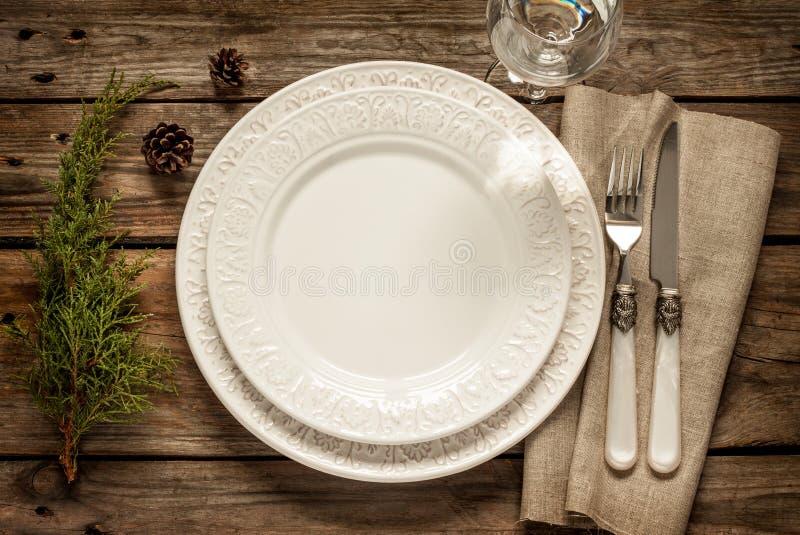 Tavola d'annata di natale - svuoti il piatto bianco da sopra su legno fotografia stock