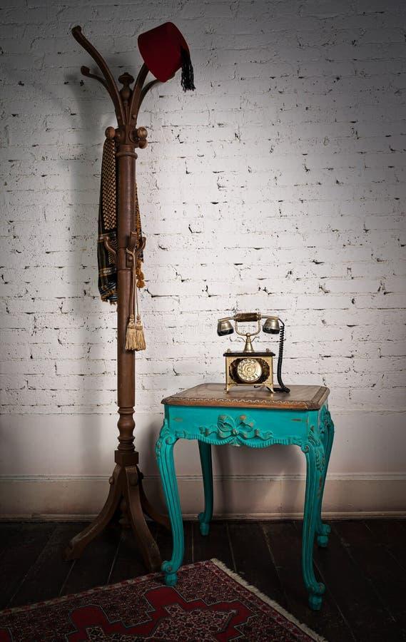 Tavola d'annata verde, vecchio apparecchio telefonico e gancio di cappotto fotografia stock