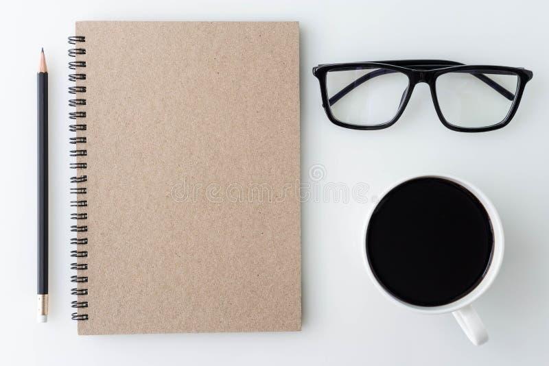 Tavola da tavolino dell'ufficio bianco moderno con il taccuino, nota, una tazza di immagine stock