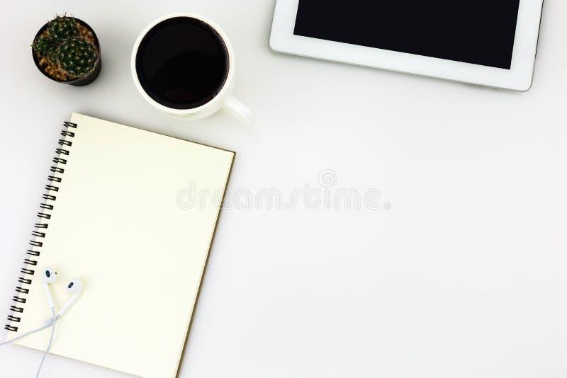 Tavola da tavolino dell'ufficio bianco moderno con la compressa, una tazza di caffè, fotografia stock