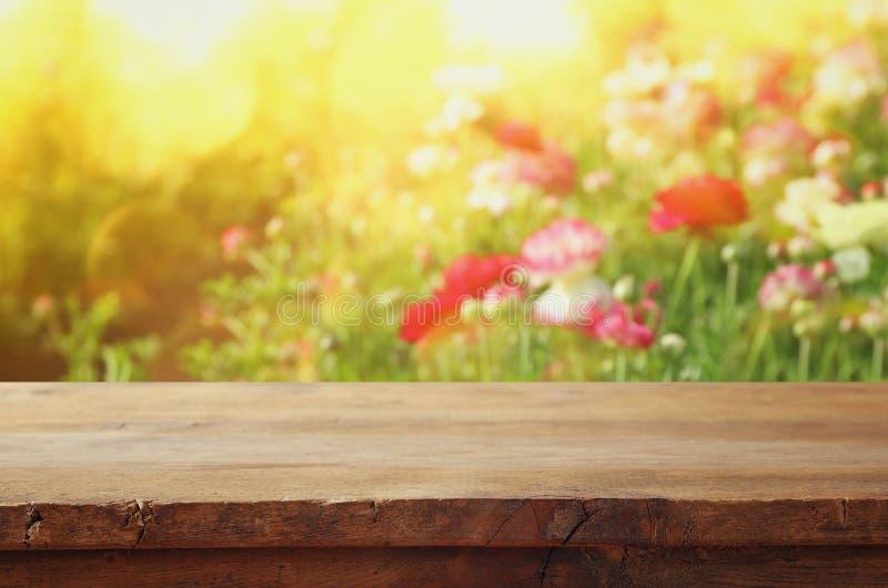 tavola del bordo di legno davanti al giacimento di fiori di estate immagini stock libere da diritti