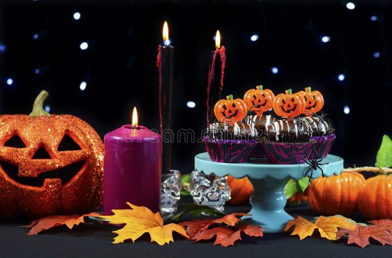 Tavola del partito di Halloween con i bigné del cioccolato, ragni, zucche fotografia stock libera da diritti