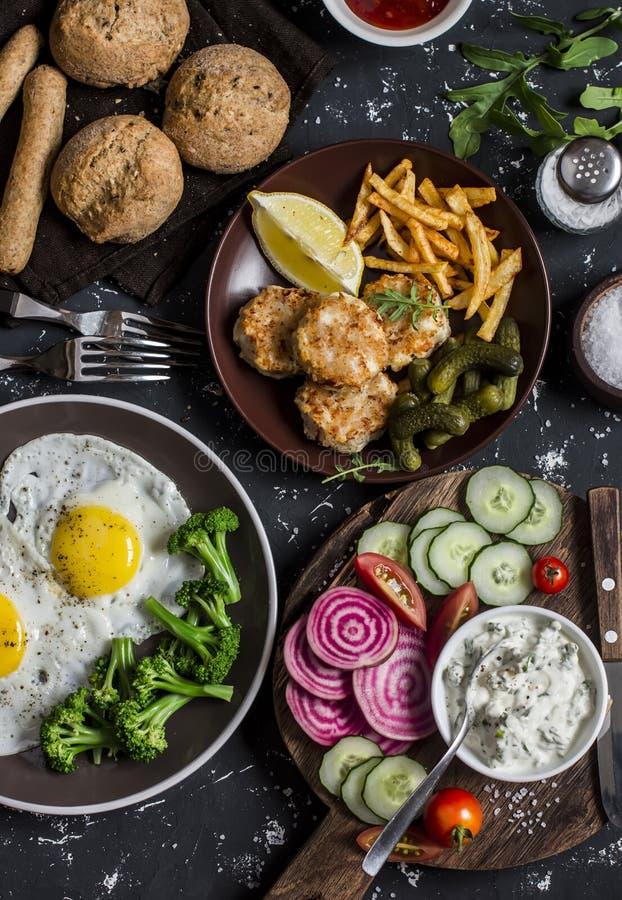 Tavola del pranzo - uova fritte, polpette del pesce, patatine fritte, verdure, salse, pane casalingo su un fondo scuro immagini stock libere da diritti