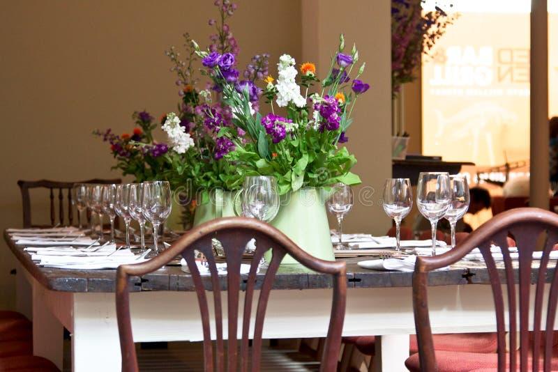 Tavola del ristorante con i fiori immagini stock libere da diritti
