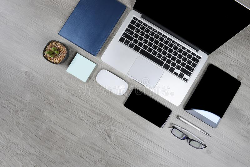 Tavola dell'ufficio con il computer portatile, il taccuino, la compressa digitale, la penna, lo smartphone, il topo, gli occhiali immagine stock