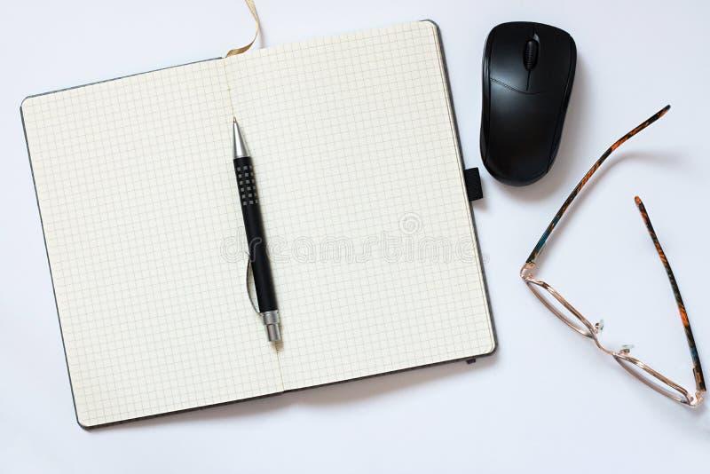 Tavola dell'ufficio con il taccuino, penna, topo, occhiali su fondo bianco Concetto da tavolino del modello dell'ufficio fotografia stock